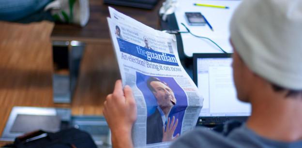 Ein Schüler liest eine englischsprachige Zeitung