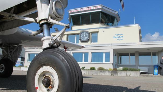 Ein Kleinflugzeug vor dem Tower des Flughafens Grenchen