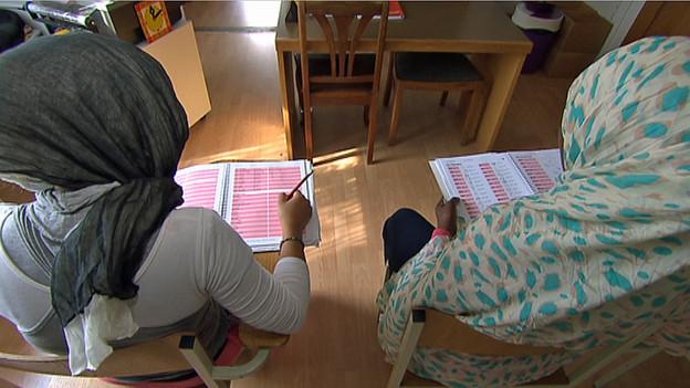 Muslimische Schülerinnen sitzen an ihren Pulten