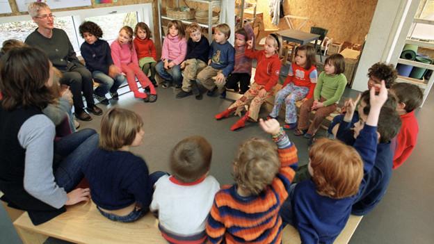Kindergärtner sitzen in einem Kreis.