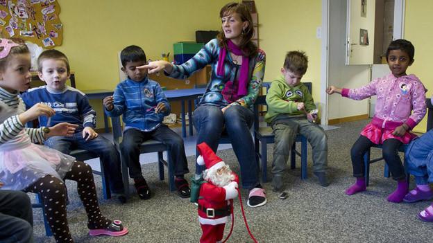 Eine Gruppe fremdsprachiger Kinder sitzt auf Stühlen.