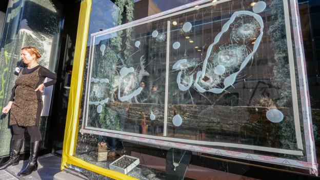 Eine Frau steht neben ihrem kaputten Schaufenster in der Europaallee.