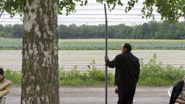 Ein Asylbewerber steht an einem hohen Zaun.