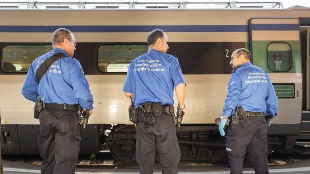 Grenzwächter stehen vor einem Zug.