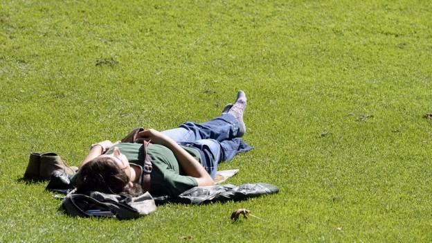 Mann liegt auf dem Rasen