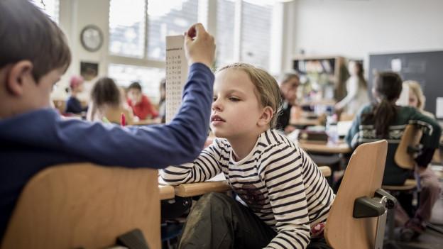 zwei Kinder schauen miteinander Rechenaufgaben an