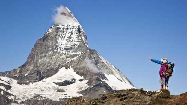 Wanderer zeigen aufs Matterhorn.