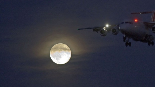 Ein Flugzeuge landet bei Vollmond.