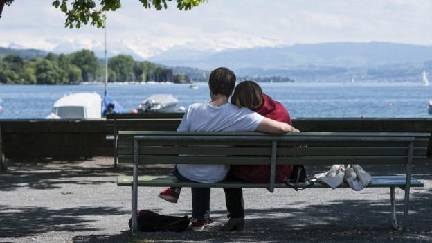 jugendliches Paar auf einer Bank am Zürichsee