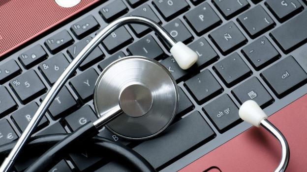 Eine Tastatur, darauf ein Stethoskop.
