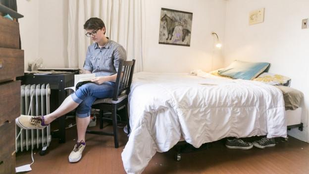 Ein junger Mann sitzt auf einem Stuhl in seiner Wohnung.
