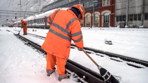 Bahnarbeiter befreien die Gleise am Bahnhof Bellinzona vom Schnee.