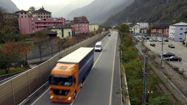 Autobahn mit Lastwagen mitten durch ein Dorf