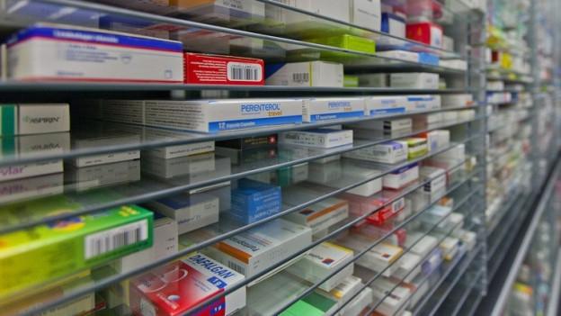 Blick in ein Regal voller Medikamente.