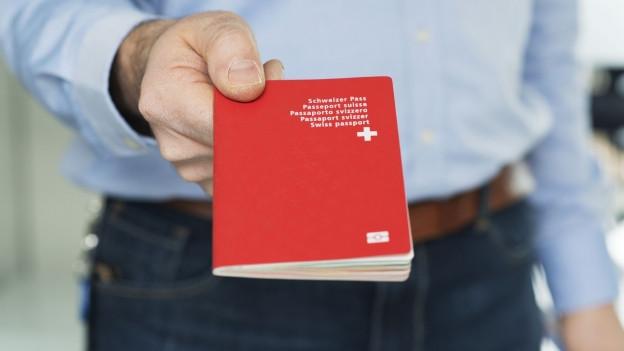 ein Mann übergibt einen roten Schweizer Pass