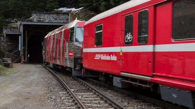 Eine rhätische Bahn fährt in den alten Albula-Tunnel.