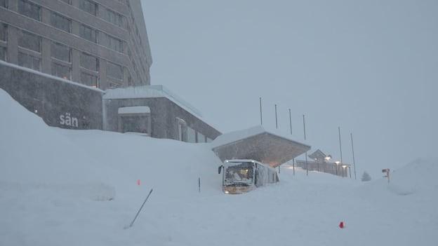 Ein Postauto, das vor lauter Schnee kaum mehr zu sehen ist.