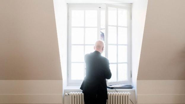 Ein Pfarrer schaut aus dem Fenster.