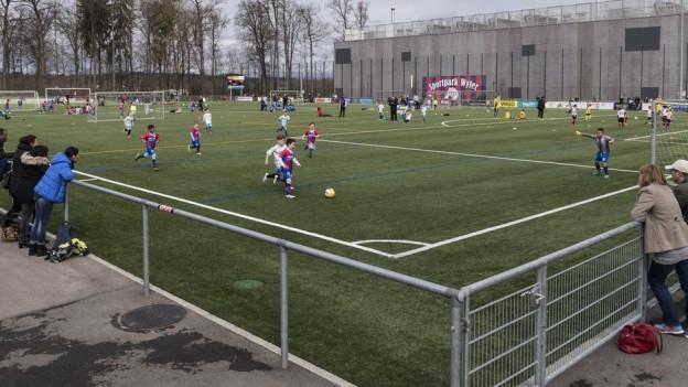 Kinder spielen auf einem Kunstrasen Fussball.