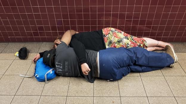Zwei Obdachlose liegen auf dem Boden.