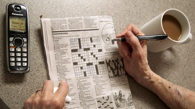 Eine ältere Frau füllt ein Kreuzworträtsel aus.