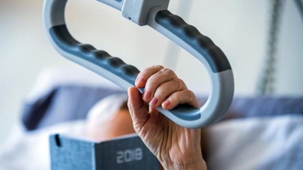 Eine alte Person hält sich in einem Pflegebett fest.