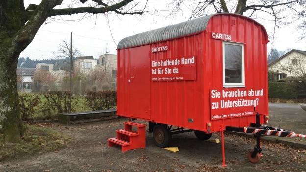 Ein roter Baustellenwagen der Caritas Schweiz