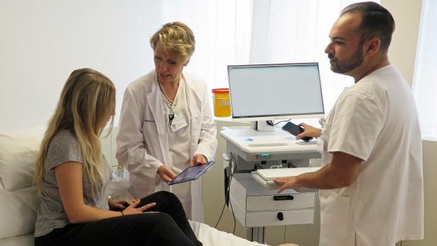 Eine Ärztin mit Tablet bei einer Patientin.