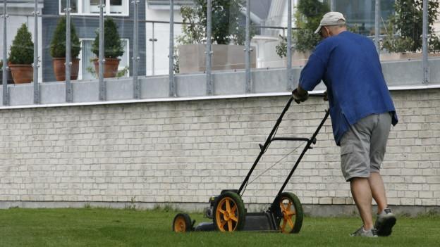 Ein Rentner am Rasenmähen.