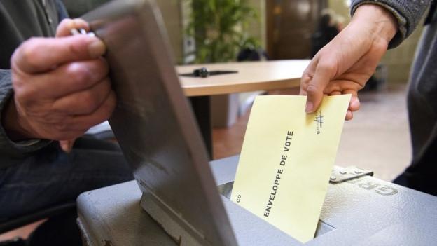 Jemand wirft seinen Stimmzettel in eine Urne.