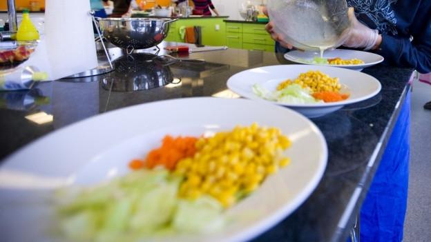 weisse Teller mit Salat auf einer Anrichte in einer Küche