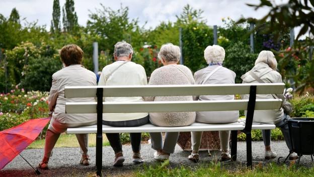 Mehrere pensionierte Frauen sitzen auf einer Bank.