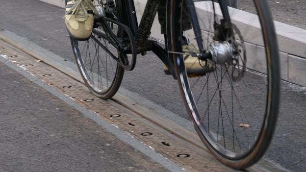 ein dunkles Fahrrad fährt in einer mit Gummi gefüllten Tramschiene