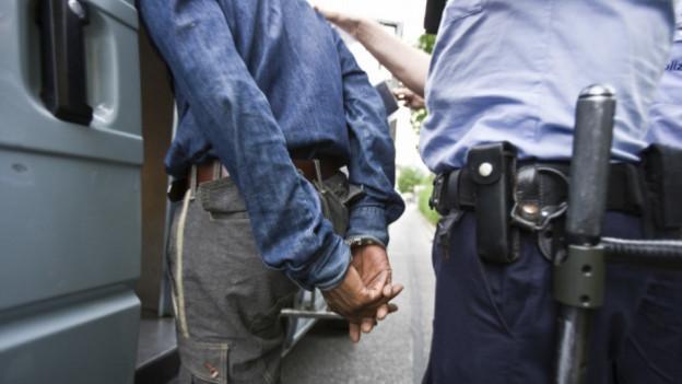 Ein Mann wird in Handschellen abgeführt.