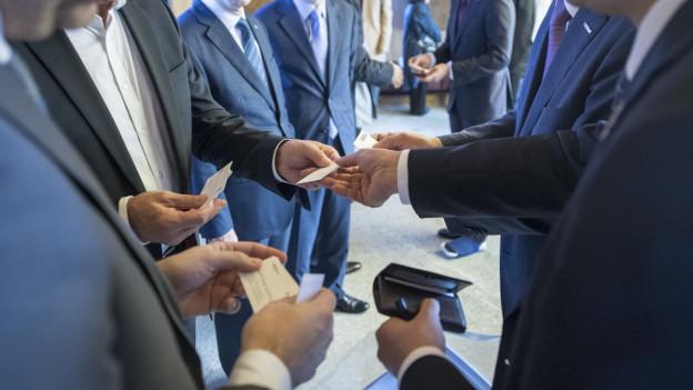 Eine Gruppe von Geschäftsmännern tauscht Visitenkarten aus.