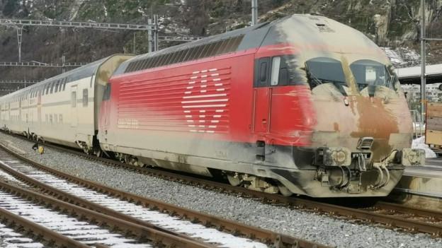 Schmutzige Lok fährt aus dem Lötschbergtunnel.