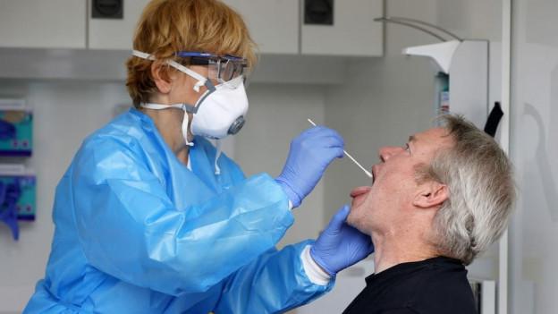 Ein Mann lässt sich von einer Pflegefachfrau einen Rachenabstrich machen.