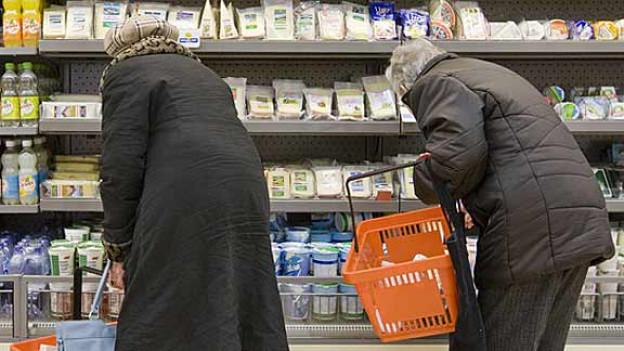 Zwei Seniorinnen bedienen sich im Supermarkt am Kühlregal.