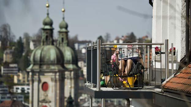 Ein Mann liest eine Zeitung auf seinem Balkon mit Blick über die Stadt.
