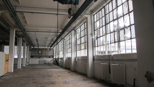 Eine ausgebrannte Halle mit zerborsteten Fensterscheiben.