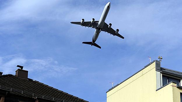 Flugzeug dicht über bewohntem Gebiet