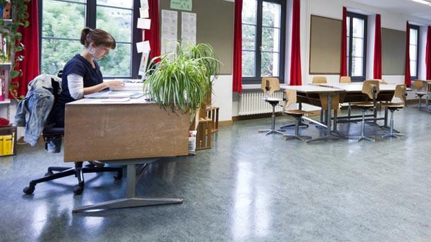 Eine Lehrerin sitzt an ihrem Pult in einem leeren Schulzimmer.