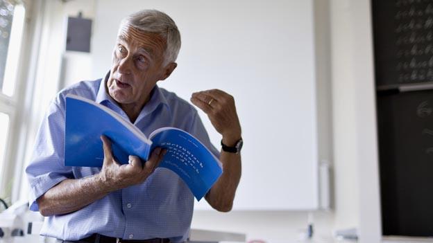 Ein älterer Lehrer hält ein Buch in der Hand und unterrichtet vor einer Klasse.
