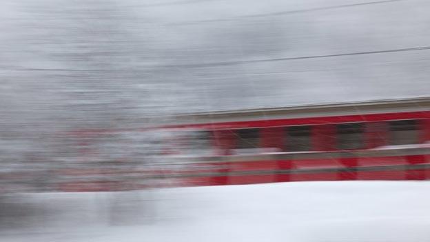 Eine Bahn fährt im Schnee am Fotografen vorbei