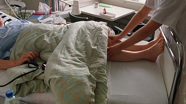 Eine Pflegerin massiert eine Patientin. (Symbolbild)