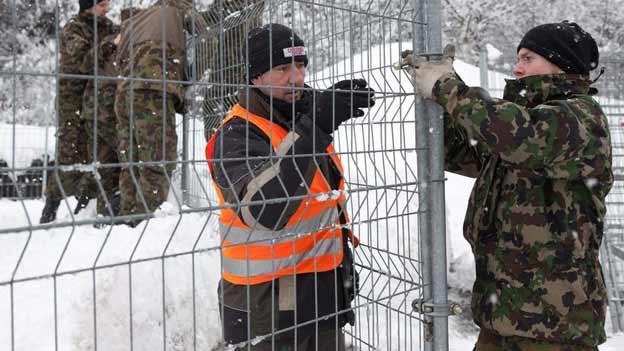 Soldaten fixieren einen Gitterzaun in Davos
