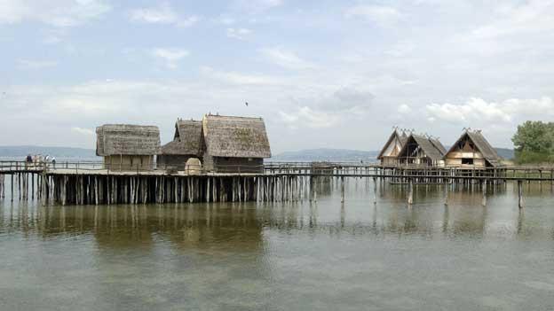Pfahlbauerhütten im See bei schönem Wetter