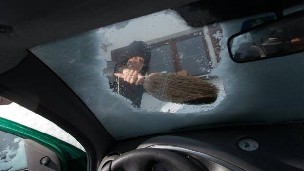 Vor dem Losfahren muss dieses Auto in Igis GR vom Schnee befreit werden.