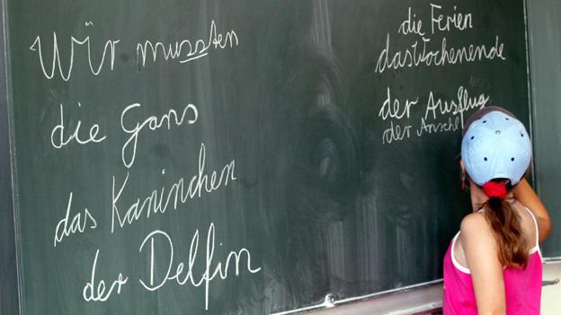 Eine Schülerin schreibt auf die Wandtafel