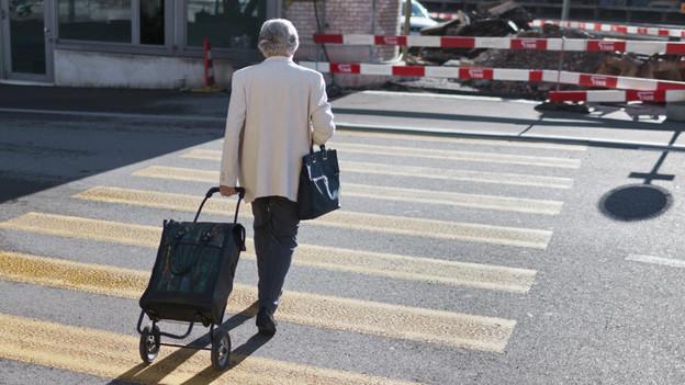 Eine alte Frau überquert die Strasse